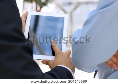 Image of two young businessmen using touchpad - stock photo