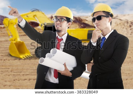 Image of two young engineers looking at the construction site with blueprint and excavator