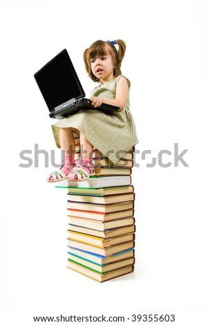 Image of typing preschool girl while sitting on top of book stack - stock photo