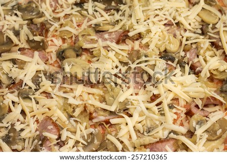 Image of unbaked pizza with bacon and mushrooms, close-up - stock photo