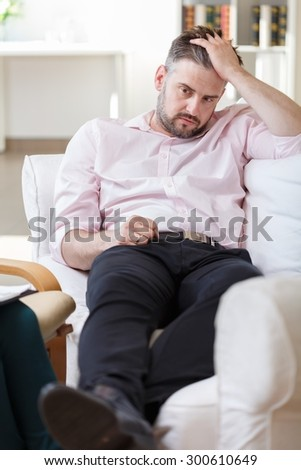 Image of unhappy male with mental problem during psychotherapy - stock photo