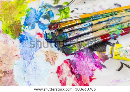 Image of used paint brush  and tube of oil paint on oil paint palette of the artist - stock photo
