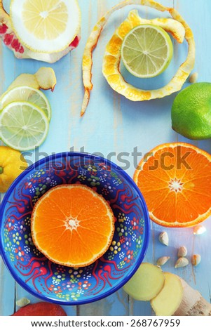 Image of various citrus fruits and ginger on blue cutting board with copyspace - stock photo