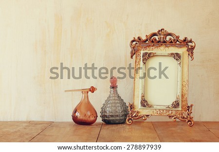 image of victorian vintage antique classical frame and perfume bottles on wooden table. filtered image - stock photo