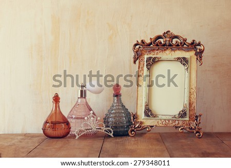image of victorian vintage antique classical frame, diamond crown and perfume bottles on wooden table. filtered image  - stock photo