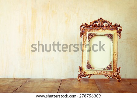 image of victorian vintage antique classical frame on wooden table. filtered image  - stock photo