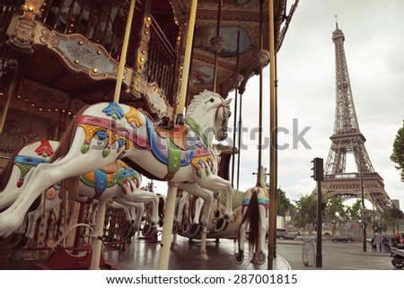 Image of vintage carousel near Eiffel tower in Paris, France. Overcast day - stock photo