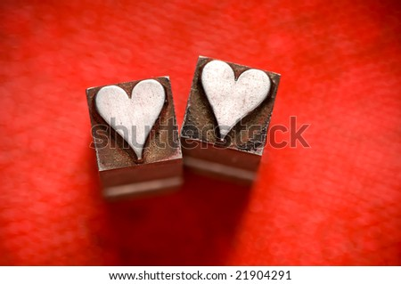 Image of vintage Letterpress Heart characters on a red texture background - stock photo