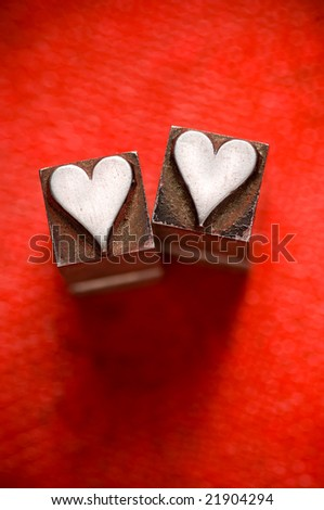 Image of vintage Letterpress Heart characters on a red texture background, narrow focus - stock photo