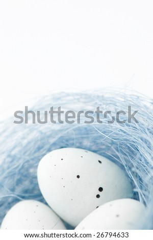 Image of white easter eggs in a blue nest, on white background.