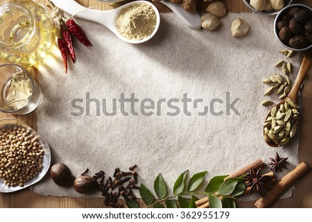 Image of white paper with spices on a wooden surface - stock photo