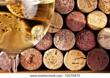 Image of wine corks through a glass of white wine. - stock photo