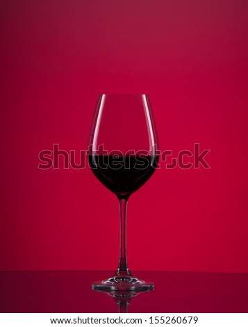 Image of wine glass with red background