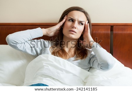 Image of woman having migraine lying in bed - stock photo