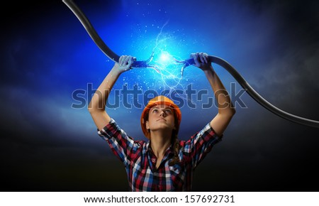 Image of woman holding electricity cable above head - stock photo