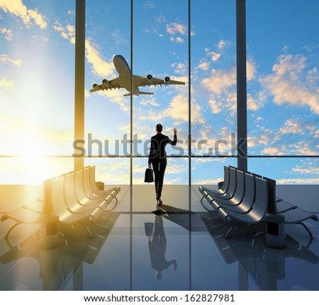 Image of woman in airport looking at taking off airplane