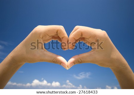Image of woman's hands made in the form of heart with blue sky