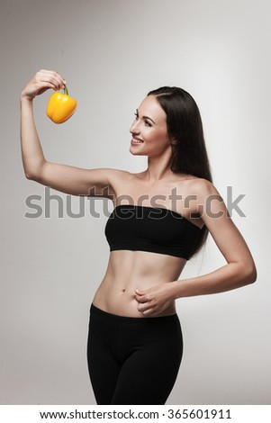Image of woman showing bell pepper. Beautiful young brunette woman with slim body looking at vegetable. Healthy eating and weight loss concept.  Studio white background. - stock photo