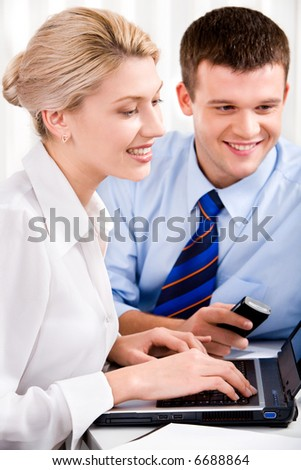Image of woman typing on the keyboard and man holding the phone - stock photo