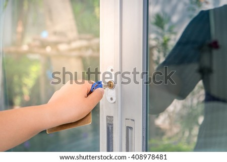 Image of woman unlock or lock front door of house with key in hand.  Selective focus - stock photo