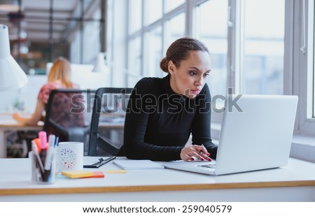 Image of woman using laptop while sitting at her desk. Young african american businesswoman sitting in the office and working on laptop. - stock photo