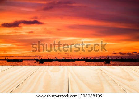 image of wood table top on sunrise over tropical sea of thailand background. can be used for display or montage your products