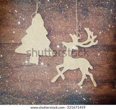 image of wooden decorative christmas tree and reindeer hanging on a rope over wooden background with glitter overlay  - stock photo