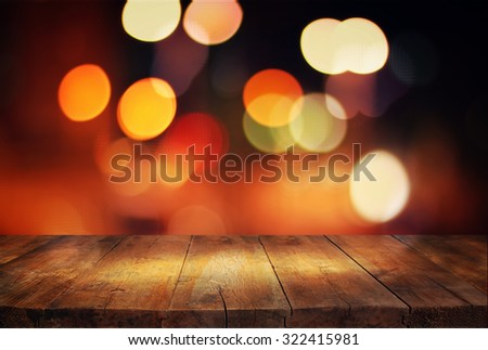 image of wooden table in front of abstract blurred background of city lights  - stock photo