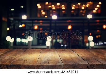 image of wooden table in front of abstract blurred background of resturant lights  - stock photo