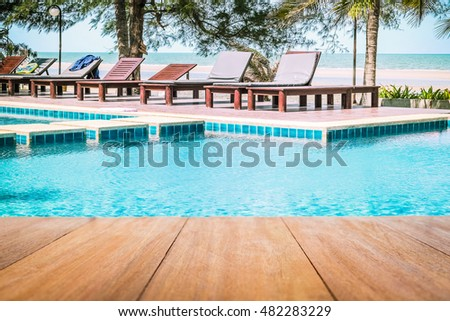 Image of wooden table in front with swimming pool in beautiful beach resort, Thailand.