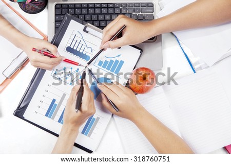 Image of worker hands pointing at business chart on the clipboard, shot at business meeting