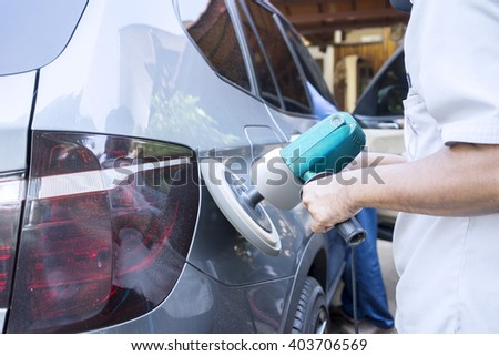 Image of worker hands polish a car body with auto polisher in the workshop - stock photo