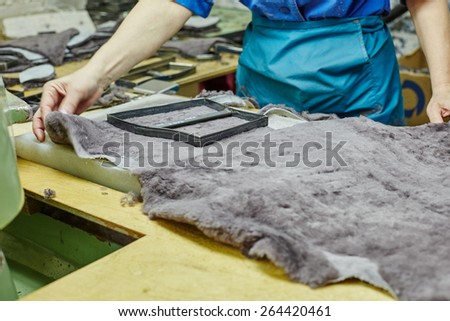 Image of worker puts templet on pelt - stock photo