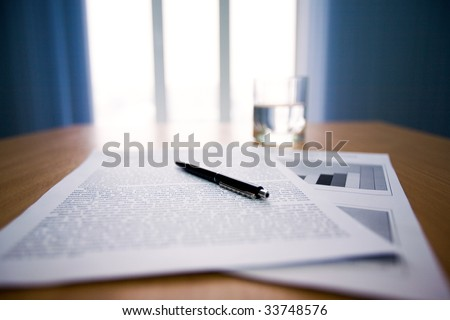 Image of workplace with focus on papers and pen on the table - stock photo