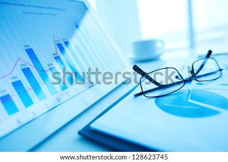 Image of workplace with paper and electronic documents and eyeglasses - stock photo