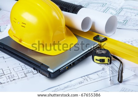 Image of yellow helmet over laptop with ruler placed on blueprint of house - stock photo