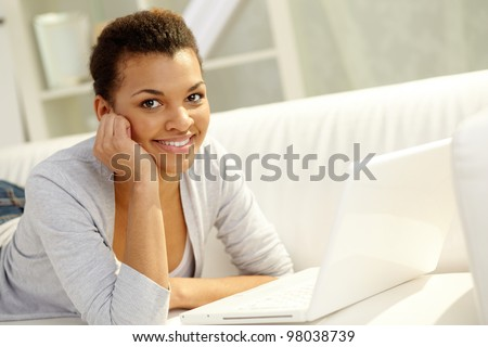 Image of young African girl looking at camera with laptop near by - stock photo