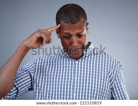 Image of young African man keeping his forefinger by head in isolation - stock photo