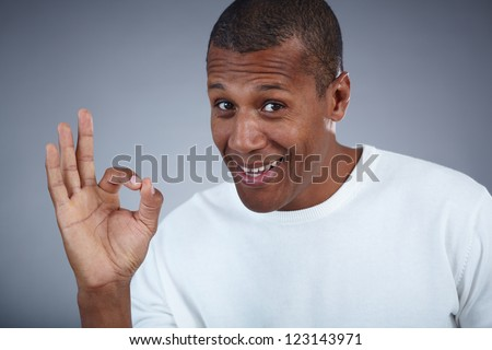 Image of young African man looking at camera while showing ok sign - stock photo