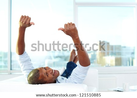 Image of young African man lying on sofa with thumbs up and looking at camera - stock photo