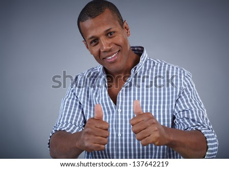 Image of young African man showing thumbs up and looking at camera with smile - stock photo