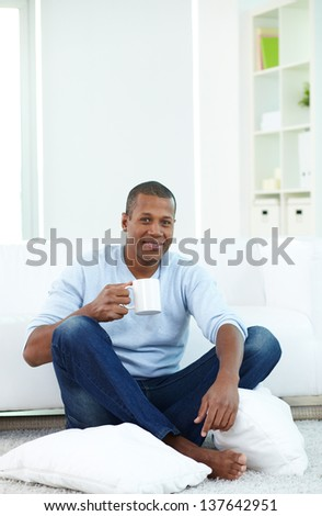 Image of young African man with cup sitting on the floor and looking at camera - stock photo