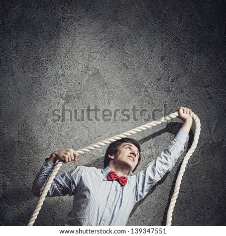 Image of young aggressive businessman holding rope