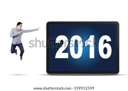 Image of young asian businessman jumping while pointing at numbers 2016 on the board, isolated on white background - stock photo