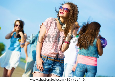 Image of young attractive woman with friends at background - stock photo