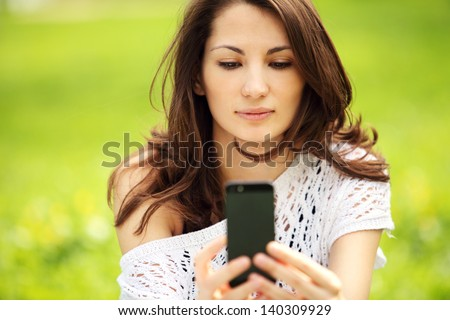 Image of young beautiful woman photographing in summer park - stock photo
