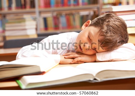 Image of young boy sleeping near books in the library - stock photo