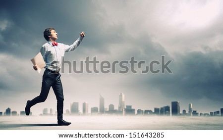 Image of young businessman against city background - stock photo