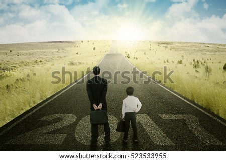 Image of young businessman and little boy looking sunlight and standing on the road with numbers 2017