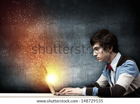 Image of young businessman at work using laptop